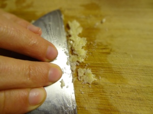 Applying pressure on knife to change texture of garlic