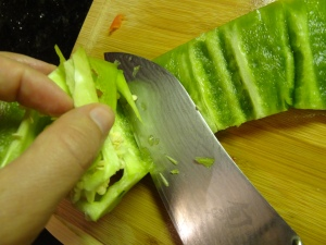 Continue to cut the pepper's inside rib around the core